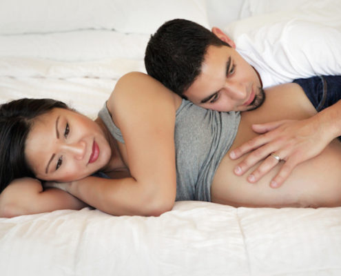 Pregnant woman lying on bed with husband